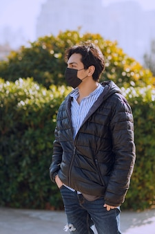 Uomo in giacca di pelle nera e maschera nera che cammina nel parco. foto di alta qualità
