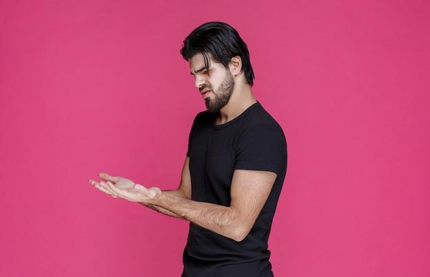 Uomo in nero che guarda alle sue mani aperte
