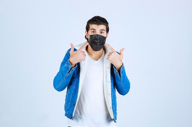 Man in black mask pointing at her mask.