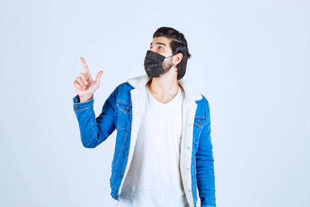 Uomo in maschera nera che punta verso l'alto.