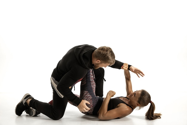 Man in black outfit and athletic caucasian woman fighting on white studio background. women's self-defense, rights, equality concept. confronting domestic violence or robbery on the street.