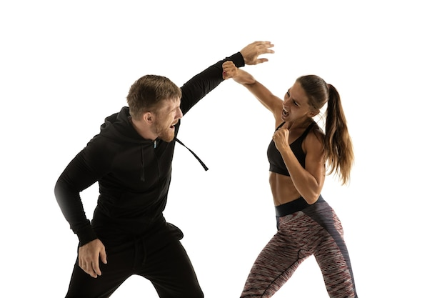 Man in black outfit and athletic woman fighting on white studio wall