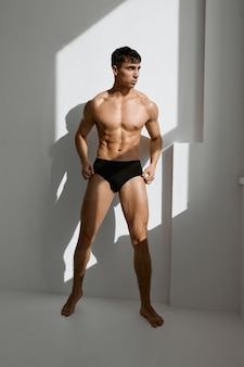 Man in black panties with a pumpedup body looking out the window
