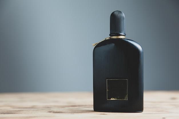 机の上の男の黒い香水瓶