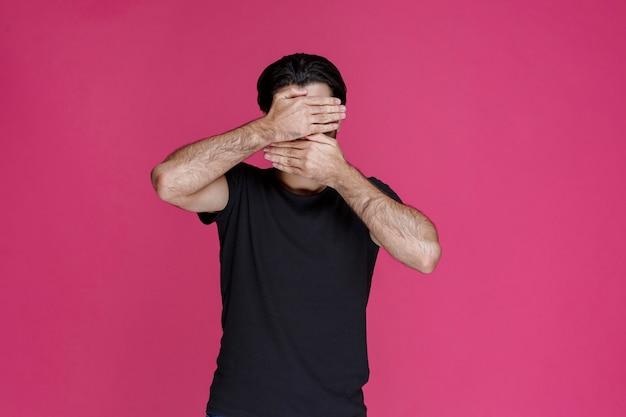 Uomo in camicia nera che chiude la sua faccia per nascondersi