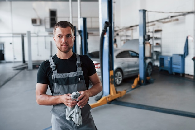 Man in black shirt and grey uniform stands in garage after repairing broken car