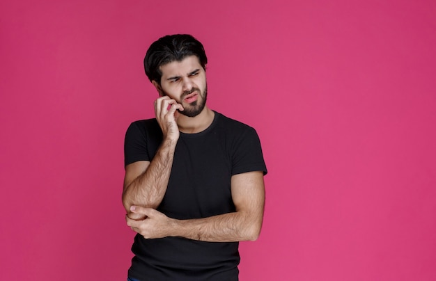 Man in black shirt looks thoughtful, confused and hesitating