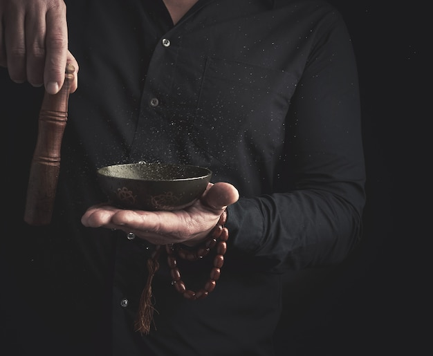 Man in a black shirt rotates a wooden stick around a copper tibetan bowl of water. ritual of meditation