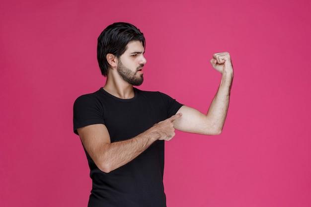 Uomo in camicia nera che mostra i muscoli del suo pugno e del braccio.