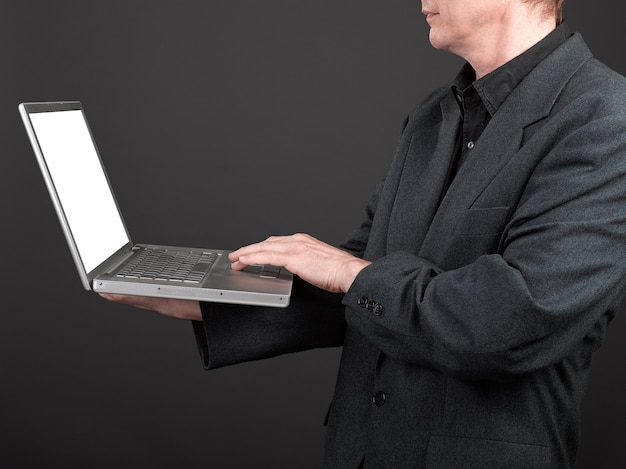 Man in black shirt and suit holding a laptop