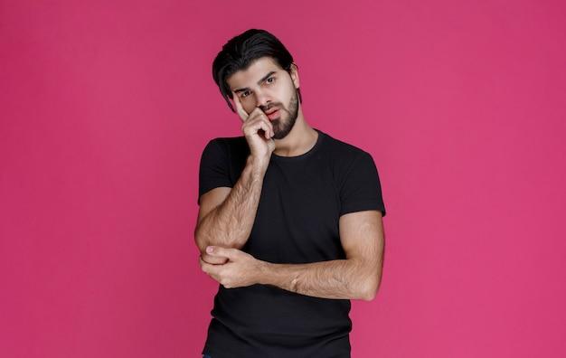 Uomo in camicia nera che pensa a qualcosa