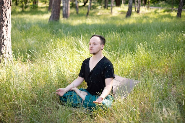 Man in black sitting lotus position practicing yoga in the park on green grass. mental health day