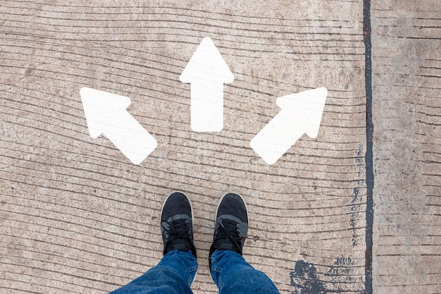 A man in black sneakers stands on a concrete road with three white directional arrows.