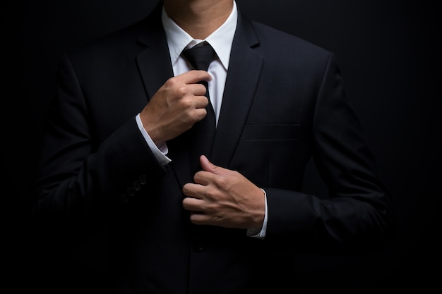 Man in black suit and adjusting his necktie