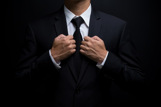 Man in black suit and adjusting his necktie