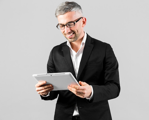 Man in black suit looking at the digital tablet
