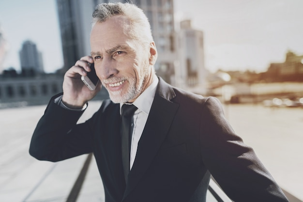 Man in a black suit talking on the phone