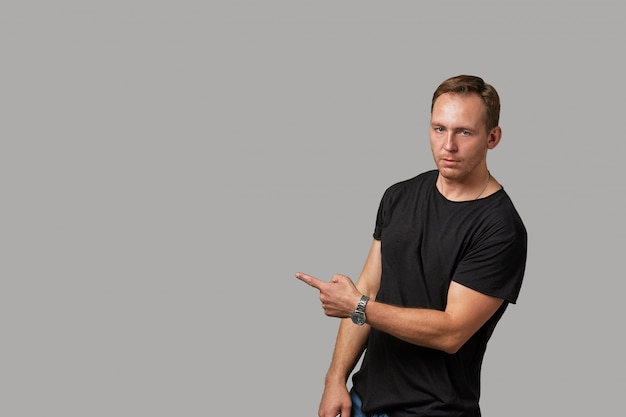 A man in a black t-shirt shows with his hands copyspace