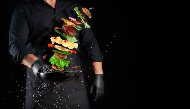 Man in a black uniform holding a cast iron round frying pan with levitating cheeseburger ingredients: sesame bun, cheese, tomato, onion, meat cutlet, pepper, copy space