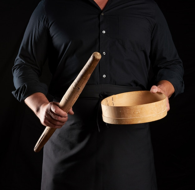 Man in black uniform holding empty vintage round wooden sieve for sifting flour and rolling pin, chef stands against black background