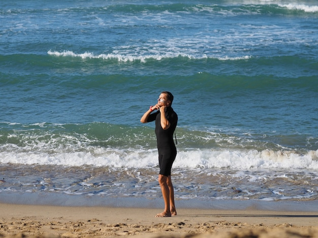 A man in a black wetsuit on the beach of the atlantic ocean.