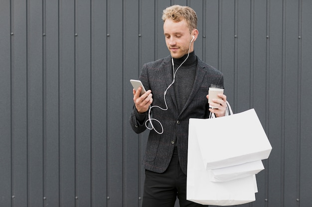 Man in black with coffee looking at smartphone