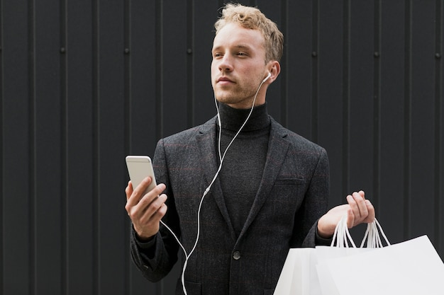 Man in black with shopping bags and smartphone