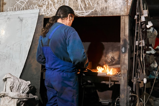 男鍛冶屋は古い鍛造の炉でワークピースを加熱します