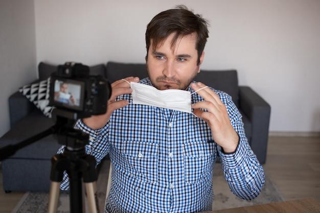 男のブロガーがコロナウイルスの医療用マスクの使い方を話します。 man recording video blogは、2019-ncovから身を守る方法を説明しています。ブロガーがmers-covにアルコールワイプ、温度計の使用方法を語る