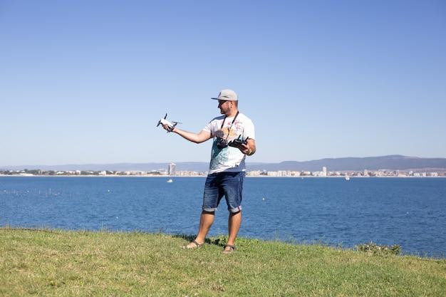 Мужчина-блогер с видео и фотоаппаратами в руках на смотровой площадке с прекрасной панорамой, снимает видео для своего блога, болгария, несебр.