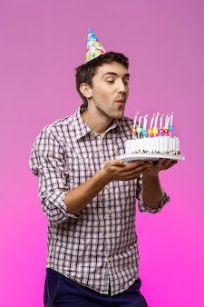 Man blowing out candles on birthday cake over purple wall.