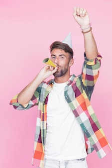 Man blowing party horn enjoying in the party against pink background