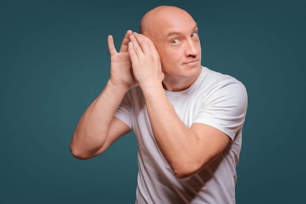 A man on a blue background in holding his hands near his ear, eavesdropping
