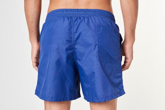 Man in blue board shorts rear view