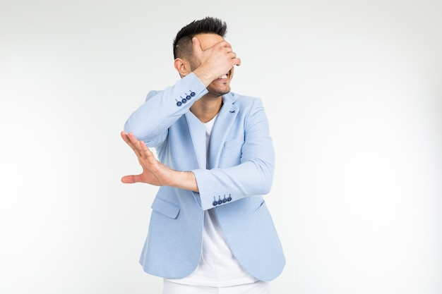 A man in a blue classic jacket closes his hand and asks to remove something on a white background