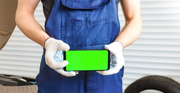 A man in a blue jumpsuit holds a phone with a green screen in a horizontal position