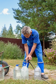 Man in a blue jumpsuit pours drinking water from a hose into large bottles. eco-friendly drinking water from a well in a country house.