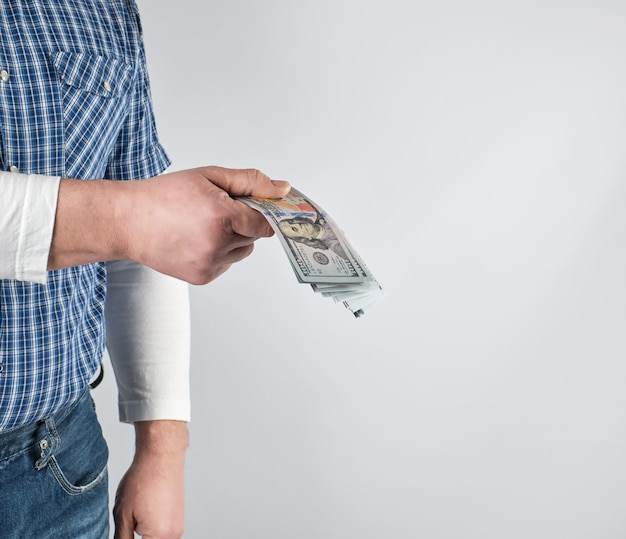 Man in a blue plaid shirt and jeans holds a stack of american paper money