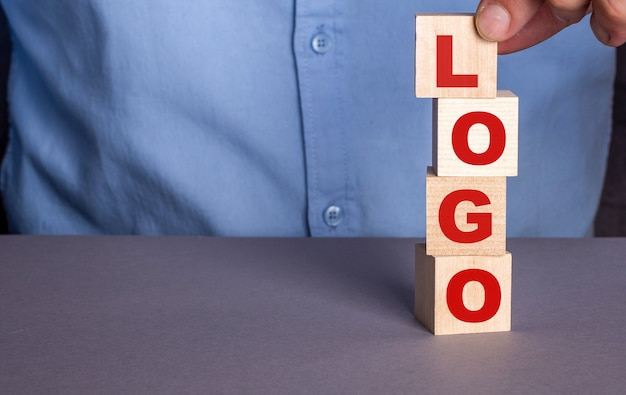 A man in a blue shirt composes the word logo from wooden cubes vertically