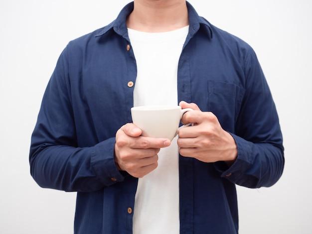 Человек синей рубашке держит чашку кофе урожай выстрел на белом фоне
