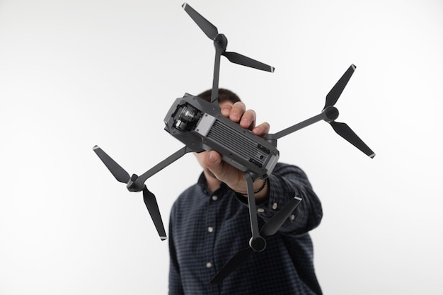 A man in a blue shirt holding a quadcopter on a white