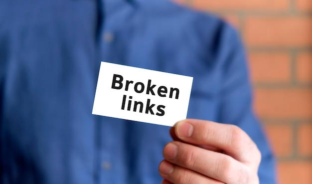 A man in a blue shirt holds a sign with the text of broken links audit in one hand