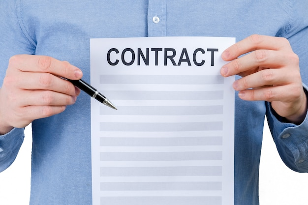 A man in a blue shirt is holding a sheet with a contract and a pen on a white background.