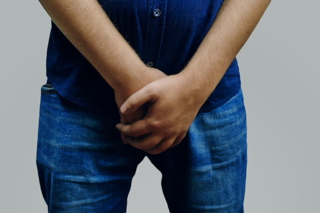 Man in a blue shirt and jeans covers his genitals with his hands