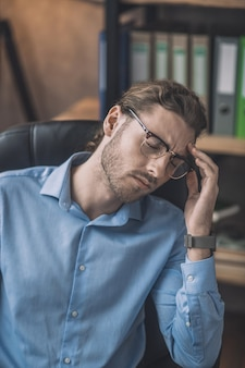 Man in blue shirt looking tired