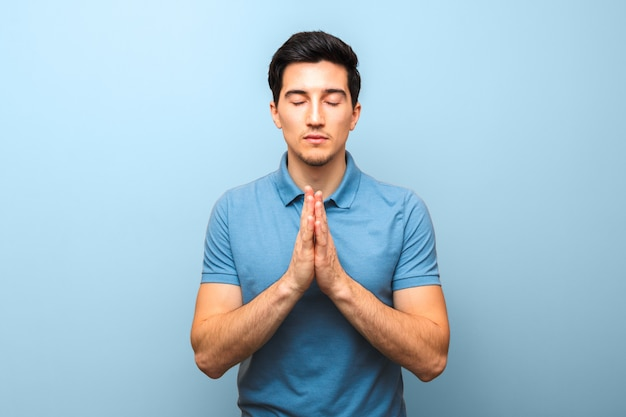 Man in blue shirt praying against blue wall