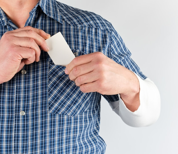 Man in a blue shirt puts in his pocket an empty blank paper business card