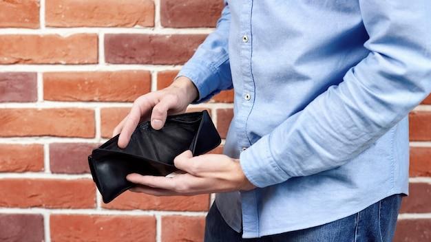 Man in blue shirt showing black empty wallet