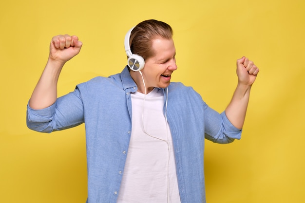 A man in a blue shirt on a yellow background dressed in white headphones and enjoys dancing music.