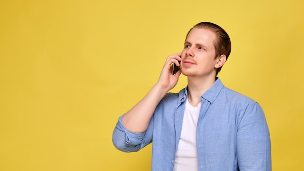 A man in a blue shirt on a yellow background is calling on his smartphone.